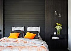 Orange velvet cushions shine against a charcoal wall