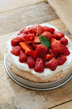 The most delicious summer Pavlova with strawberries and cream. Delicate meringue base and a creamy topping with fresh strawberries. Perfection. | jernejkitchen.com