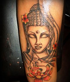 Arm tattoo of Buddha and red lotus blooms - The artist did a great job with the colors in this one.