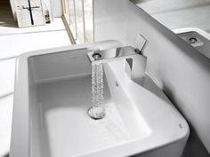 El #grifo de lavabo Singles OPEN de Roca deja que el agua caiga en una cascada cilíndrica
