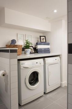 As seen on HGTV's Love It or List It, Hilary's design for this laundry room/bathroom combination includes a neutral color palette with complimentary pops of color. Functionality is apparent with front loading washer and dryer and a folding shelf above both.