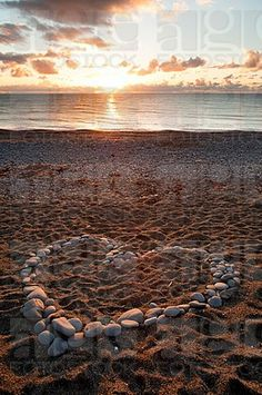 A heart shape made from pebbles at sunset on Aberystwyth beach wales UK