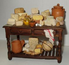 Table decorated with Italian cheeses, olive oil and olives- Artisan Handmade Miniature in 12th scale. From CosediunaltroMondo