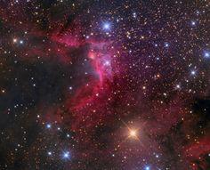 Sh2-155: La nebulosa de la Cueva.  Este colorido paisaje cósmico nos muestra las características polvorientas y el rojizo resplandor de la región de emisión Sh2-155, conocida con el nombre de Nebulosa de la Cueva