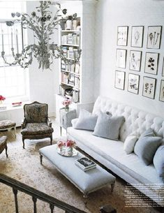 Modern french living room design. White walls with white tufted sofa and linen gray pillows! Upholstered ottoman, white Hollywood Regency chandelier and gorgeous photo gallery finish the room! White living room! White cream gray blue living room colors.