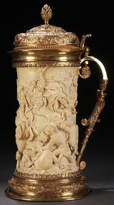 GERMAN CARVED IVORY AND GILDED SILVER MOUNTED TANKARD, 19TH CENTURY. The sides finely carved in high relief of an ancient battle scene with horses and elephants, probably depicting the battle of Zama (202BC). The flared base repoussed with rams heads, florals and fruits. The attached scroll handle with human form and the hinged lid repoussed with florals, masks and pinecone finial.