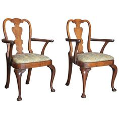Pair of Early 18th Century Mahogany and Walnut Burl Queen Anne Armchairs     Pair of circa 1725 Queen Anne armchairs made of mahogany with burl walnut backsplat and apron. Chairs have scroll carving on arms and front pad feet .   OF THE PERIOD: Queen Anne   PLACE OF ORIGIN: England   DATE OF MANUFACTURE: 1725   PERIOD: Early