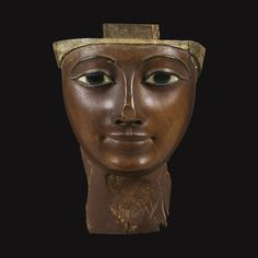 AN EGYPTIAN WOOD MUMMY MASK, 21ST/26TH DYNASTY, CIRCA 1075-600 B.C.    from an inner anthropoid coffin, carved in a fine-grained hardwood, the oval face with finely outlined lips rounded at the corners, long almond-shaped inlaid eyeswith tapering cosmetic lines, andfinely archedtapering eyebrows merging smoothly with the contour of thebridge of the nose, the central part of the wig and tenon for attachm