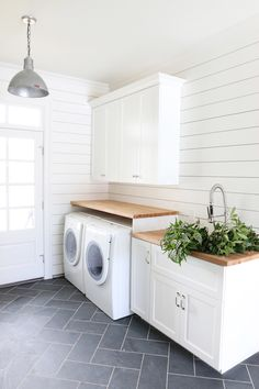 Stunning laundry room features walls clad in white paneling painted Benjamin Moore Simply White line&; Stunning laundry room features walls clad in white paneling painted Benjamin Moore Simply White line&; Laundry Room Tile, White Laundry Rooms, Farmhouse Laundry Room, Laundry Room Storage, Laundry Room Design, White Rooms, Coastal Farmhouse, Modern Coastal, Basement Laundry