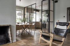 Vardagsrummet och matsalen binds samman av sin ekparkett och är centrerade kring en öppen spis. Gungstolen av Hans J Wegner är en prototyp.
