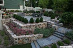 Raised bluestone patio with boxwood hedge and fieldstone retaining ...