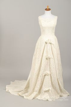 Designed in the 60's, this beautiful vintage wedding gown is done in a creamy white floral lace over an acetate lining in the bodice and lace over a layer of tulle with an acetate lining in the skirt.