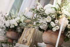 Terracotta urns retain the rustic feel and frame the alter perfectly