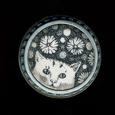 "Cynthia Toops. ""Flower Creature - Cat""  Brooch in sterling silver and polymer clay with ink illustration. 1.25"" in diameter."