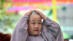 - Criança sul-coreana reage depois de ter sua cabeça raspada por monges budistas durante uma cerimônia, no templo Jogye, em Seul. Foto: Jung Yeon-Je / AFP