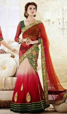 Red and Beige Net Embroidered Lehenga Saree Look demure yet ravishing wearing this red, beige and orange shaded net lehenga saree. Decorative pattern and applique decked lower part and waist line lends looks. Decorative patterned border and stick on crystal embellished second half spruces charm. Comes with a matching stitched round neck blouse with 6 inches sleeves. #RedNetLehengaSaree #LehengaStyleSareesOnline