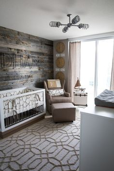 Serene Travel Themed Nursery: A simple wood-paneled wall and some neutral furniture are all it takes to make this nursery feel like its own little cabin in the woods. Bonus: Once baby grows up, you've got the perfect man cave.