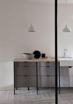 Carl har selv utformet den røffe kjøkkenmodulen i rustfritt stål sammen med danske Frama. Rammene i svart plukkes opp igjen i form av den svarte jernsøylen midt i rommet, mens benkeplaten i eik og håndtakene i lær gir helheten en myk finish. Delikat! Kitchen Columns, Moduler Kitchen, Module Design, Grey Stuff, Stainless Steel Kitchen, Office Desk, Corner Desk, Interior, Table