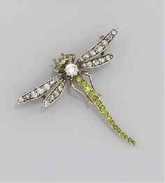 AN EDWARDIAN, DIAMOND, DEMANTOID GARNET AND ROSE-CUT DIAMOND NOVELTY BROOCH modelled as a dragonfly, with old-brilliant-cut diamond single stone body, demantoid garnet tail and eyes, and rose-cut diamond wings
