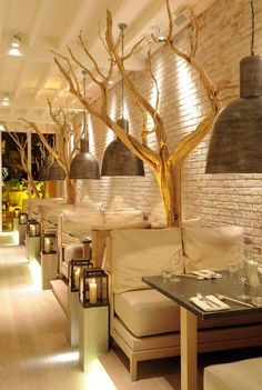 Restaurant design; Bricks painted white, branches and lanterns...pretty cool booth option!