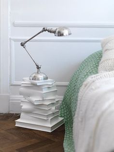 stack of books as nightstand with lamp on it next to bed