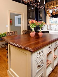 Black and cream cabinetry mixed with wood countertop