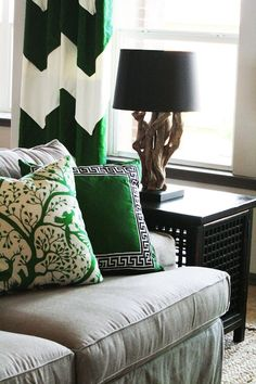 Gorgeous tan & green living room design with white & green chevron herringbone drapes, tan linen slip-covered sofa, black lattice Asian end table and green pillow with Greek key trim.