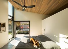 This master bedroom has a sloped cedar ceiling and a wide pocket door opens it up to the backyard.