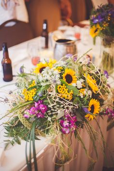 The reception flowers were a combination of local wildflowers surrounding the wedding venue that were featured in the bouquets, boutonnieres and hanging sunflower pomanders at the ceremony.