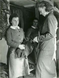 NHdH receiving a new uniform.  Interesting to see the sweater styles being worn by the Helferin in their work smocks.  Also the Helferin on the right is wearing a wool gabardine uniform instead of the traditional wool fabric.