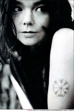 Björk --- Note the lovely Viking symbol on her Left arm. It is the SYmbol of the Gods / of the Elements / & it's a religion that was alive & well until ROME forced Norway into Christianity -- many Vikings retreated after fighting for their religious freedoms for literally centuries -- and off they went to ICELAND. in 1973 the old religion was reinstated as Valid & common.