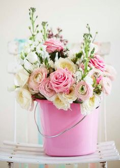 A pretty pink bucket of flowers.