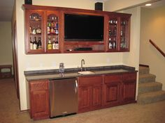 We turned this old, rundown basement into a Man Cave. This basement included this wet bar, complete with custom cabinetry, built in TV, and mini-fridge. In a secondary Showcase you can see the Main Bar and Living areas, including 7 more TV's, full fridge and custom shelving,