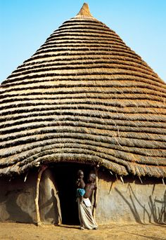 Africa | Dinka children in front of a hut.  South Sudan | Dinka settled homesteads are made of mud and covered with conical thatched roofs. They are built in single- or two-story styles, and  if single, another is built in close proximity to store grain or house an extended family. | ©Carol Beckwith and Angela Fisher