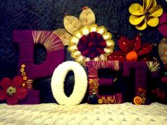 """Yarn covered letters spelling """"POET"""" with multicoloured yarn, felt flowers and a variety of new and vintage buttons"""