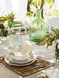 Vajilla blanca, copas y jarras de cristal y una damajuana verde sobre la mesa del porche