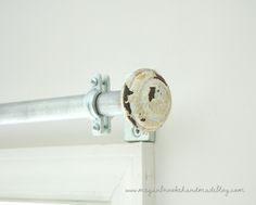 Curtain rod made from elecrical conduit, split ring hangers, and old door knobs. By Megan Brooke Handmade