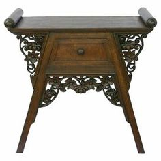 "Hand-carved teak wood end table with floral embellishments and 1 drawer.  Product: End tableConstruction Material: Teak woodColor: BrownFeatures:  Hand-carvedOne drawerEmbellished with floral carvings Dimensions: 26"" H x 26"" W x 13"" D"