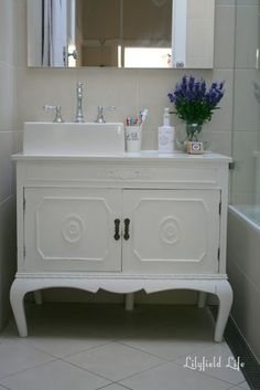 Erinn Valencich found an old cabinet at a flea market and repurposed it as an antique bathroom vanity, bringing a charming look to this bathroom.