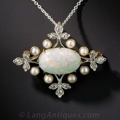 This Edwardian era delicacy - circa 1910 - is designed around an enchanting set oval opal, weighing 2.75 carats (measuring 7/16 inch across), glowing with bright pastel colors. The gemstone is framed by eight lustrous half pearls and four diamond-set trefoil foliate motifs. Beautifully hand fabricated in platinum over 18K yellow gold, this thoroughly lovely pin/pendant necklace combo measures 1 1/4 wide by just over 1 inch high. The platinum chain measures 18 inches.