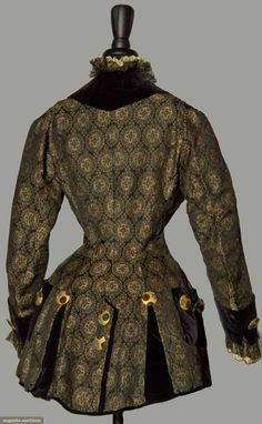 Black silk ground w/ Persian inspired brocade, small rondels in metallic gold, sky blue, maroon & yellow, fitted torso, constructed in style of gent's 18th C jacket, black velvet trim & back pockets, cream & gold embroidered lace trim, 24 magnificent gold metal buttons inset w/ cut steel faceted beads in silver, cobalt & wine, bright yellow silk satin lining,