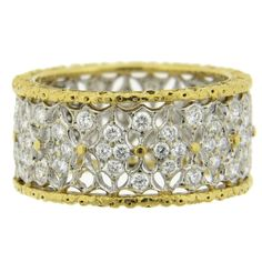 An 18k white and yellow gold band ring set with approximately 0.55ctw of H/VS diamonds. DESIGNER: Buccellati MATERIAL: 18k Yellow Gold GEMSTONE: Diamonds DIMENSIONS: Ring is a size 5, 8.9mm wide. WEIG