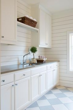 Clean lines and crisp whites define the laundry room. The gray-and-white checked…