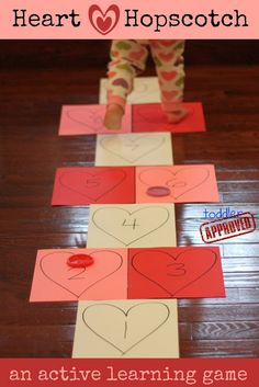 We made our game by drawing hearts onto cardstock, adding numbers, and then taping the paper to the floor with painter's tape. We tossed plastic playdough lids instead of rocks. There are a lot of different versions of hopscotch you can play... we just made up our own and practiced identifying and saying the names of the numbers with our toddler while hopping. S http://www.toddlerapproved.com/2013/01/simple-indoor-activities-for-kids.html