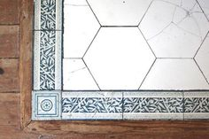 """The hearth of this fireplace is made of hexagonal field tiles with a border of 3"""" x 6"""" border tiles in an Anglo-japanese bamboo design in teal blue, with 3"""" x 3"""" square complementary tiles to turn the corner."""