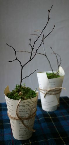 A paper cup wrapped in book pages can hold handmade paper flowers or twigs