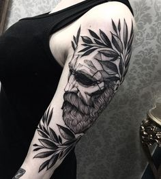 Artistic sleeve tattoo. The tattoo shows a man, who is presumably a scholar with a crown of leaves on his head. He seems to be closing his eyes as he bows down in front of him.