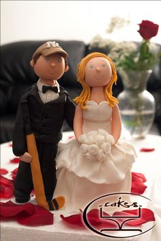 I made this custom cake topper for a couple getting married this weekend. The bride's dress was based off of her actual wedding dress. The groom loves hockey - so he requested that I make a hockey stick and him wearing his favorite Yankees hat.