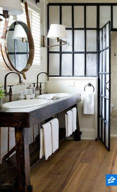The bare, crisp white walls and ceiling and country-style sinks in this bathroom are reminiscent of an outdoor bathhouse and sauna. Vintage-style towel holders make the vanity country-perfect, and the rustic, dark-stained wood make the whole thing stand out. Simple swing-arm sconces complete the look – keeping things low-key and soft.