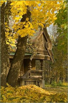 A pretty picture of what looks like a extravagantly built log cabin in the forest. Either way, the outside de'cor is beautiful and interesting.